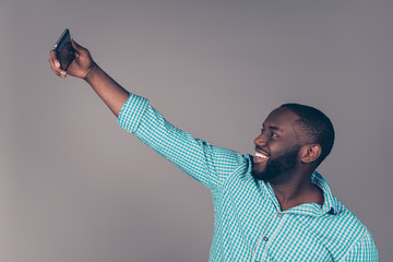 Portrait of happy afroamerican  bearded  man makes selfie photo and smiling