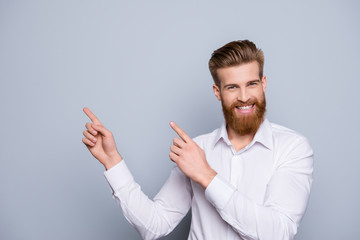 Portrait of serious confident bearded man pointing with fingers on copy space and smile Wall mural