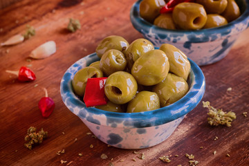 Preserves green olives in ceramic bowls with chili, oregano. Close-up