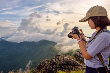 Hiker asian teens girl wear caps looking photo on digital camera is beautiful landscape natural of sierra and sky during sunset on mountain at Phu Chi Fa Forest Park, Chiang Rai, Thailand