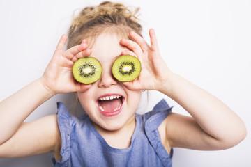 Beautiful girl child holding kiwi