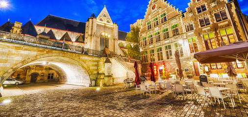 GENT, BELGIUM - MARCH 2015: Tourists visit ancient medieval city at night. Gent attracts more than 1 million people annually