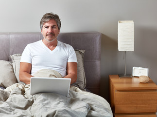 Man with laptop in bed.
