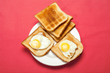 Toasts and eggs on a plate on a red table