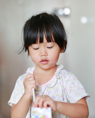 Closeup of little girl drinking milk with straw.
