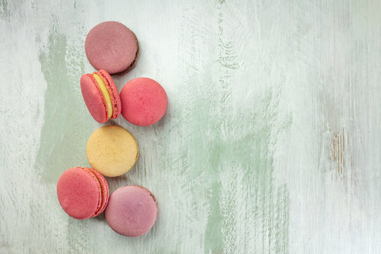 Vibrant macarons on light teal texture with copyspace