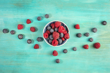 Fresh blueberries and raspberries on turquoise background with c
