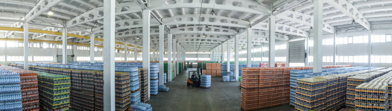 panoramic view of a large warehouse with drinks in plastic bottles with loading machines