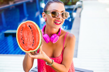 Close-up of a fashionable portrait of a happy cute girl holding half a red watermelon against a pool background and laughing, smiling and listening to music in large pink headphones. Perfect smile
