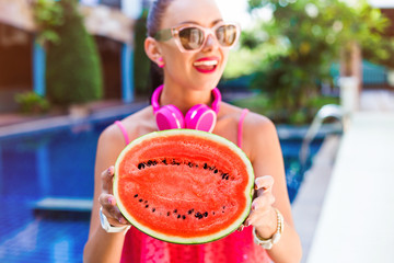 Close-up of a fashionable portrait of a happy cute girl, holding half a red watermelon and laughing, smiling and listening to music in large pink headphones. Blue pool, perfect smile, white teeth