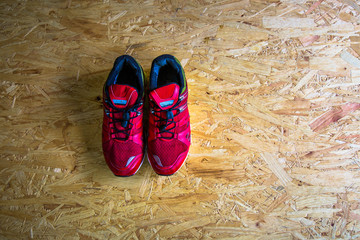 Red sneakers on wooden background