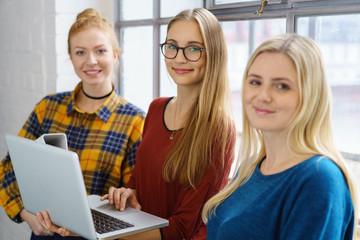 drei moderne junge frauen mit laptop
