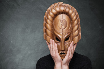 A person wearing wooden mask yin yang symbolizing harmony holding his hands on the mask standing over gray background. Philosophical sense. Dark and light sides of life.
