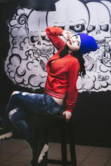 Young beautiful woman on background of the graffiti on the wall in the room of sexy, fashionable