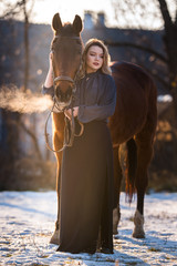 Young beautiful elegance woman posing with horse