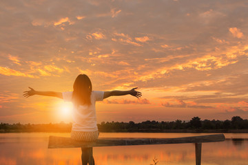 Woman Celebration Success Happiness Relaxed on a Wooden Evening Sky Sunset at the Lake Background, Sport and active life Concept.
