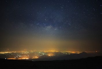 Milky way galaxy and city light at Phutabberk Phetchabun in Thailand.Long exposure photograph.With grain