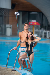 Beautiful couple - guy and girl with perfect figure posing against the swimming pool with perfect aqua water and taking selfie photo with monopod on the luxury resort