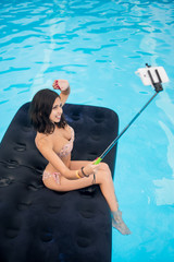 Profile of a young brunette makes selfie photo on the phone with selfie stick on mattress in pool. Copy space. View from above