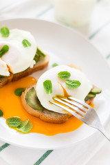 Vegetarian breakfast: avocado toast with poached eggs, orange juice, yogurt and jam on white wooden background. Selective focus