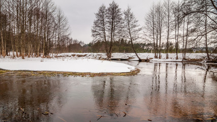 February thaw. Beautiful winter landscape. Small snow island on the forest river