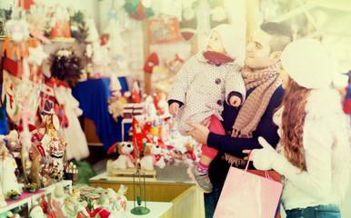 Happy family choosing Christmas decoration at Christmas market.