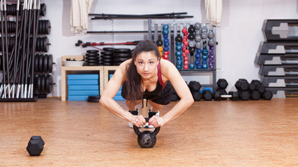 woman sports push up on kettlebell
