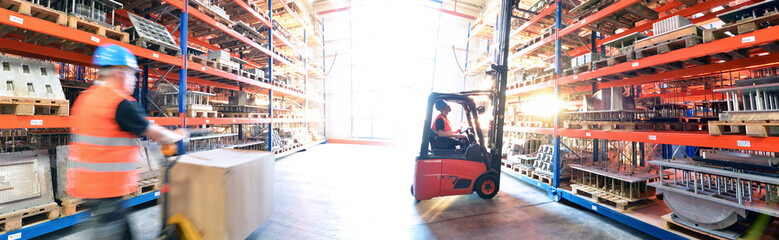 Logistik im Warenlager - Arbeiter mit Hubwagen und Gabelstapler am Hochregal // Logistics in warehouse - Worker with pallet truck and forklift truck on high rack