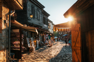 People walk through pedestrian cobblestone streets of ancient Nessebar with cafe, restaurant and souvenir shops at sunset.