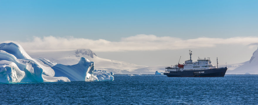 Blue cruise vessel among the icebergs with glacier in background, South Shetland Islands, Antarctica