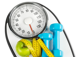 measuring tape green apple dumbbell on white bathroom scale fitness concept background isolated / fitness waage maßband apfel konzept hintergrund