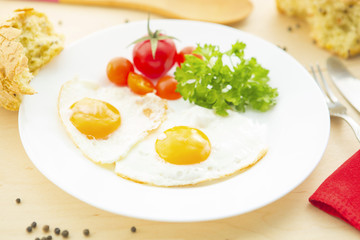 Fried Eggs on a plate on wooden background