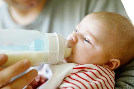 Father feeding newborn baby daughter with milk in nursing bottle