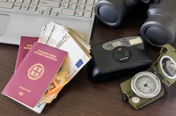 Two passports, a camera, a computer and money. Concept - preparation for travel.