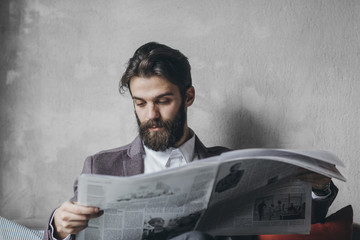 Handosme businessman with beard reading newspapers at cafe.