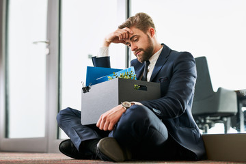 Fired from work. Sad dismissed businessman sitting outside the office after losing his job