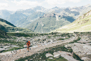 Hiker with backpack running on a mountain trail