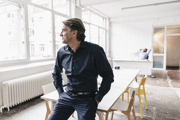 Mature businessman looking out of window in run down office