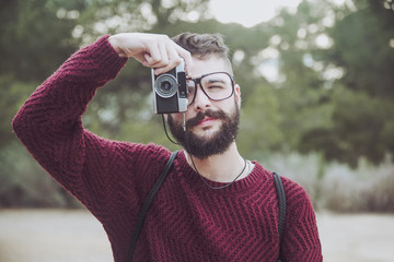 Portrait of bearded man with glasses taking photo with vintage camera
