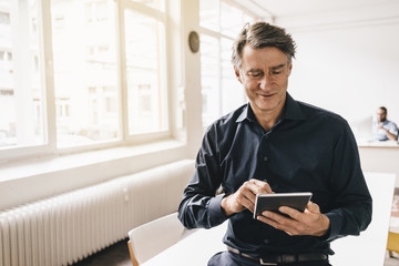 Mature businessman using tablet in office