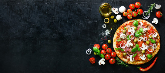 Food ingredients and spices for cooking mushrooms, tomatoes, cheese, onion, oil, pepper, salt, basil, olive and delicious italian pizza on black concrete background. Copyspace. Top view. Banner.
