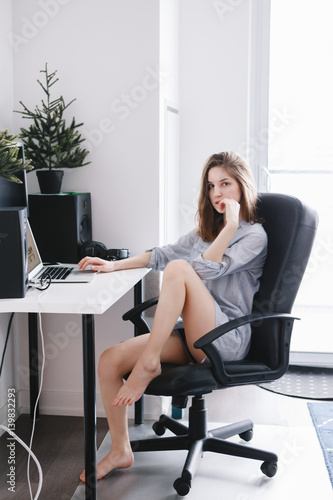 097d0ba331 Portrait of young beautiful Caucasian girl woman student in pajamas shirt  working on laptop computer sitting in office chair at home
