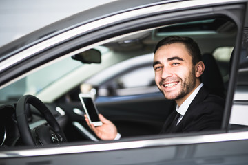 Businessman in car use smartphone and smile on camera