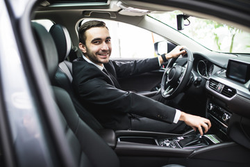 transport, business trip, destination and people concept - close up of young man in suit driving car look at camera Fototapete