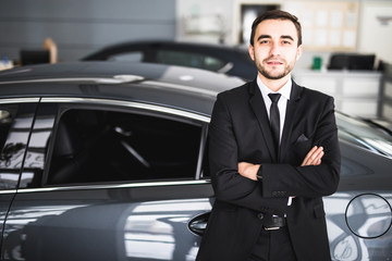 Handsome young classic car salesman standing at the dealership