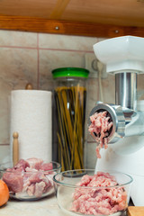 Home electric meat-grinder is making pork stuffing in a modern kitchen. Pork stuffing in a glass bowl.