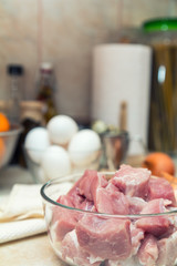 Raw pork neck meat cut in slices on glass bowl. Shallow depth of field. Toned.