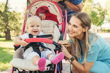 Young mother talking to smiling baby in pink stroller. Parents walking outdoors with child in summer pram.