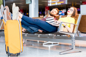 Young couple sleeping on the chairs at the waiting room of the airport. Long waiting for the airplane