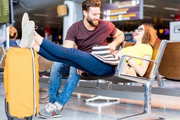 Young couple in colorful t-shirts sitting with baggage at the waiting room of the airport